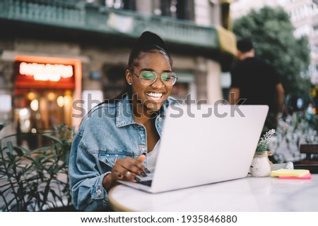 Joyful dark skinned female blogger typing text of publication using laptop computer working remotely, cheerful African American woman in spectacles share positive content and media files on netbook Stock photo ©