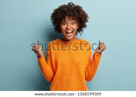 Joyful dark skinned model with crisp hair, clenches fists, feels overjoyed after winning game, wears orange jumper, poses over blue background, expresses good emotions. People and success concept