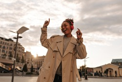 Joyful dark-skinned woman in oversized beige trench coat and eyeglasses smiles, listens to music and dances outdoors.