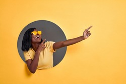 Joyful dark skinned woman points fingers aside , pleased by big sale prices, wears sunglasses and casual orange t shirt, models over yellow background, shows copy space for your advert.