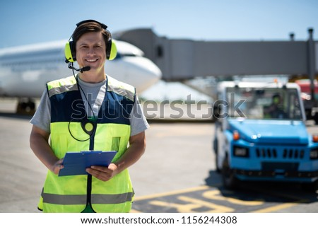 Joyful day at airport. Waist up portrait of smiling airport worker. Car, plane, sky and runway on blurred background