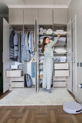 Joyful domestic female putting box on shelf in cupboard enjoying housework at wardrobe. Happy housewife organizing storage in closet at comfortable home. Smiling woman in pajamas arranging clothes