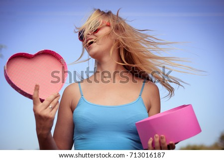Joyful excited lovely woman holding heart shaped gift box in hands. Happy smiling surprised young lady over light blue sky background. Excitement beauty celebrating moment #713016187