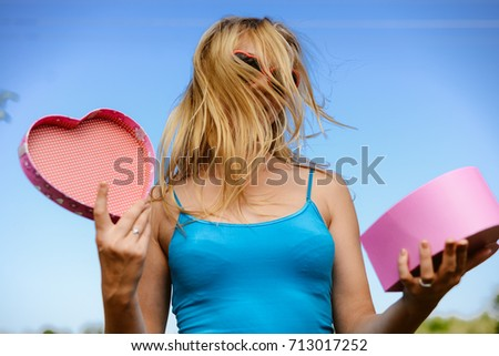 Joyful excited lovely woman holding heart shaped gift box in hands. Happy smiling surprised young lady over light blue sky background. Excitement beauty celebrating moment #713017252