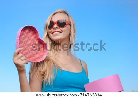 Joyful excited lovely woman holding heart shaped gift box in hands. Happy smiling surprised young lady over light blue sky background. Excitement beauty celebrating moment #714763834