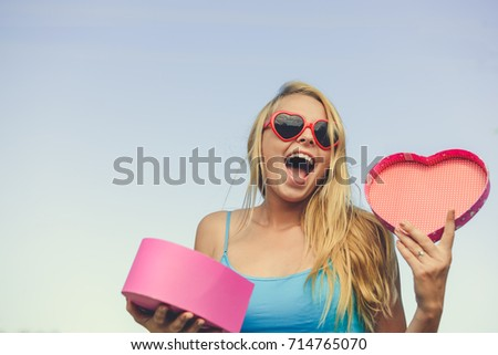 Joyful excited lovely woman holding heart shaped gift box in hands. Happy smiling surprised young lady over light blue sky background. Excitement beauty celebrating moment #714765070