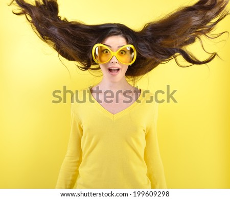 Joyful excited surprised young woman with flying hair and big funny glasses over yellow background.