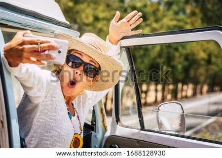 Photo of Joyful expression for beautiful caucasian adult traveler woman taking selfie picture with a smart phone during alternative travel vacation with old van vehicle - vanlife concept and free people