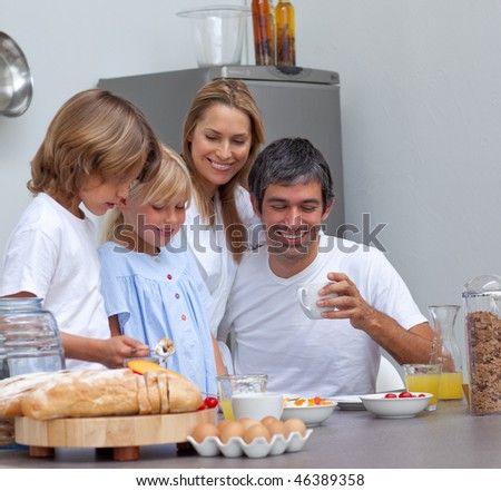 Joyful family having breakfast in the kitchen