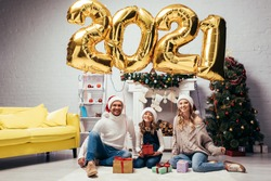 joyful family in santa hats sitting near presents and shiny balloons with 2021 numbers