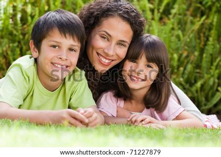 Joyful family lying down in the garden at home