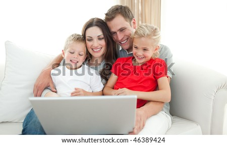 Joyful family using a computer sitting on sofa in the living room