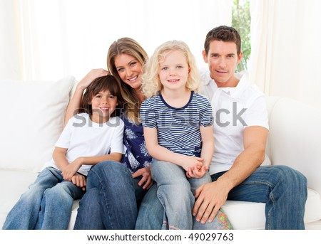 Joyful family watching television sitting on sofa at home