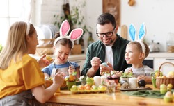 Joyful family wearing bunny ears headbands gathering at table in modern light kitchen and paining Easter eggs together