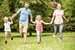 Joyful family with two children have fun running in the park