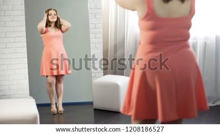 Joyful fat female in dress admiring her mirror reflection, enjoying being plump ストックフォト ©