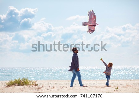 joyful father and son, family launching the kite on sandy beach, at windy day