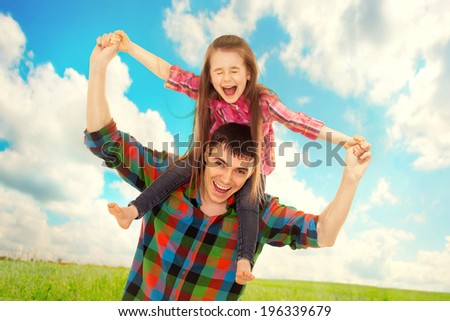 Joyful father with daughter on shoulders carefree and happy. Fathers day, family holiday, vacation