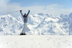 joyful female skier rising her hands up at mountain background
