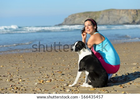 Joyful fitness woman with dog on beach taking a break from running. Sporty girl with her pet on summer sport  and relaxing day.