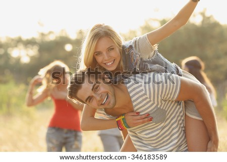 Joyful friends relaxing, a girl on guy's back in the forest outdoors #346183589