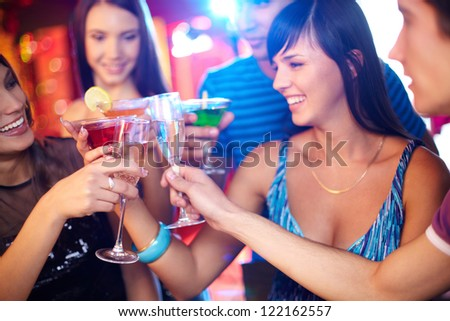 Joyful friends toasting at birthday party with focus on champagne flutes