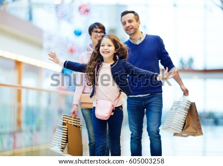 Joyful girl and her parents enjoying weekend in the mall