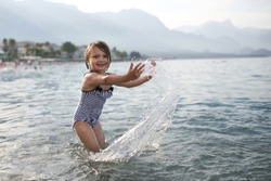 joyful girl child splashing in the sea, the child splashes water on a pebble beach in Turkey. Summer, vacation and sea concept, happy childhood, gray tone