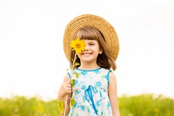 Joyful girl in hat smiling and covering face with sunflower in summer field