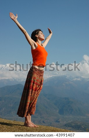 Joyful girl over the mountains with outstretched arms. Early in the morning.