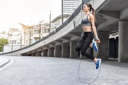 Joyful girl skipping on rope near stadium