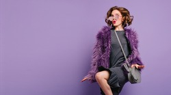 Joyful girl with curly brown hair dancing on purple background with kissing face expression. Indoor portrait of barefooted woman in black dress and fluffy jacket.
