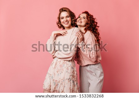 Joyful girls expressing happiness on pink background. Front view of two well-dressed ladies smiling at camera.