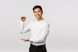 Joyful good-looking asian male entrepeneur, employee in white shirt, pants, showing big box with pleased expression, holding product or something large and satisfying, stand white background
