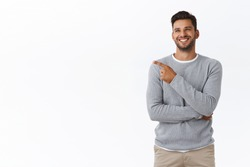 Joyful good-looking friendly nice bearded guy in grey sweater, laughing from funny joke or advertisement, smiling carefree and delighted, chatting with friend and pointing left, white background