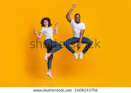 Joyful guy and girl jumping in funny poses, interracial couple having fun together over yellow background in studio, free space