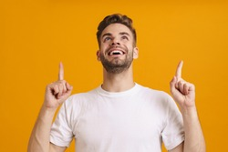 Joyful handsome unshaven guy smiling and pointing fingers upward isolated over yellow background