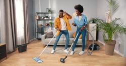 Joyful happy African American young married couple wife and husband cleaning living room and dancing, guy mopping and woman vacuuming floor having fun making funny rhythmic moves in cozy modern home