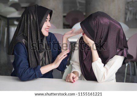 joyful, happy islamic woman talking with smile and laugh; islam or muslim happy women chatting, talking with her friend; asian 20s woman model with hijab or islamic head scarf