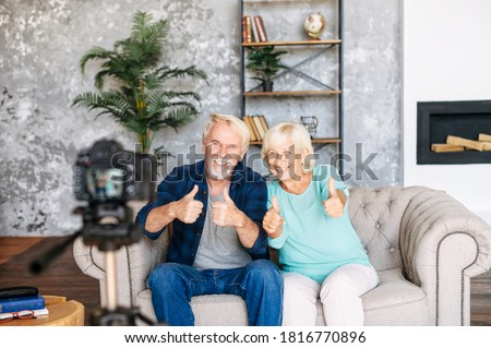 Joyful happy senior couple is recording video blog in the cozy living room. Elderly modern spouses are shoving thumbs up into camera on tripod in front of them Foto stock ©