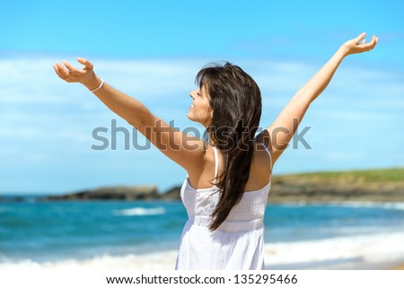 Joyful happy woman raising arms to the sky on summer. Beautiful and blissful caucasian girl on beach vacation. Playa de Verdicio, Asturias, Spain.