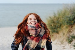 Joyful happy young redhead woman wearing a warm winter scarf looking up into the air with a beaming smile as she strolls on a sandy beach in the dunes