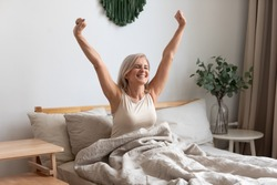 Joyful healthy older woman sitting on bed, waking up after good night rest on comfortable orthopedic mattress, rising up arms and stretching back. Happy mature grandma feeling energetic in morning.