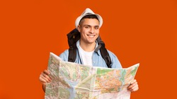 Joyful hiker with big backpack holding map over orange studio background
