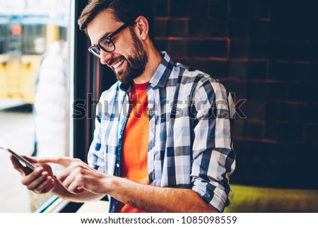 Joyful hipster young man in eyewear typing text message on smartphone device.Positive student reading funny notification and chatting in social networks on telephone via free 4G internet connection