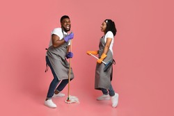 Joyful Housekeeping Concept. Portrait Of Cheerful African Couple Of Cleaners Having Fun During Chores