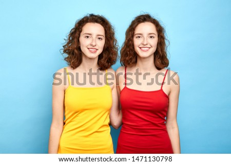 joyful identical positive stylish twins in red and yellow dresses looking at the camera. close up photo. isolated blue background, lifestyle, double beauty, people