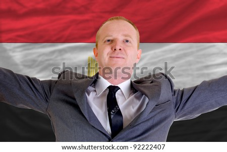 joyful investor spreading arms after good business investment in egypt, in front of flag