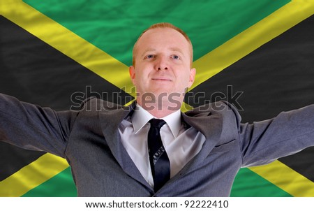 joyful investor spreading arms after good business investment in jamaica, in front of flag