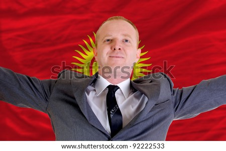 joyful investor spreading arms after good business investment in kyrghyzstan, in front of flag